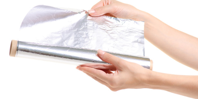 Foil roll in hand on white background isolation